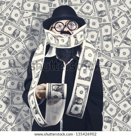 Billionaire male business person making money on the roll when covered in one dollar USD bills. Financial success concept