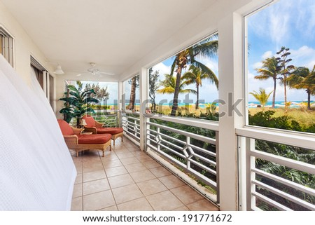 Billowing white curtains on a sunny screen in porch with an oceanfront view - stock photo