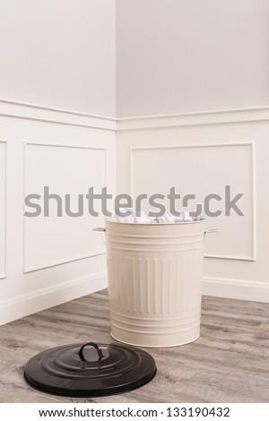 bin with paper waste on wooden floor in cozy room - stock photo