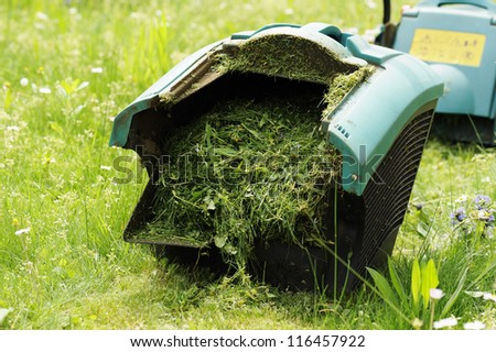 binder lawn mower full of lawn grass - stock photo