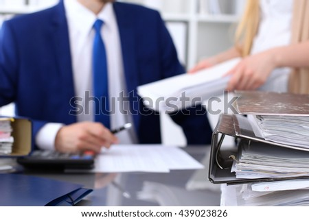 Binders with papers are waiting to be processed with businessman and secretary back in blur. Accounting planning budget, audit, insurance  concept - stock photo