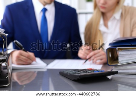 Binders with papers are waiting to be processed with businessman and secretary back in blur. Internal Revenue Service inspector checking financial document.  - stock photo