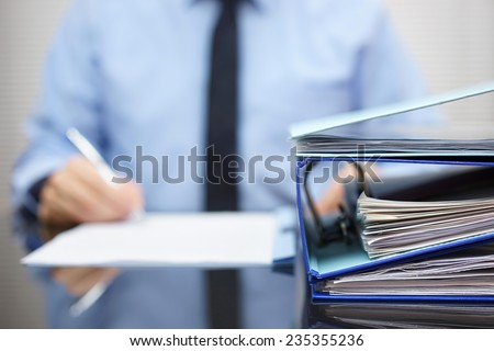 binders with papers are waiting to be processed with businessman  back in blur. Accounting and business concept - stock photo