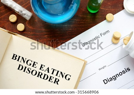 binge eating disorder  written on book with tablets. Medicine concept.