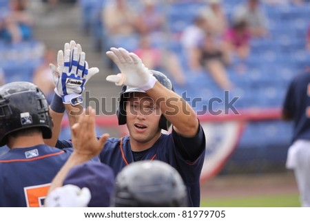 BINGHAMTON, NY - JULY 7: Binghamton Mets batter Matt Den Decker receives high fives after belting a home run in a game against the Portland Sea Dogs at NYSEG Stadium on July 7, 2011 in Binghamton, NY - stock photo