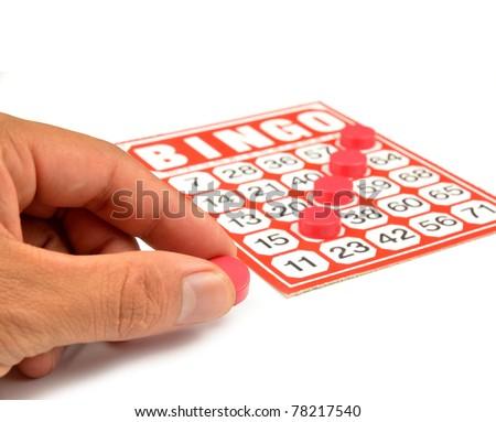 bingo card with hand hold winning chips - stock photo