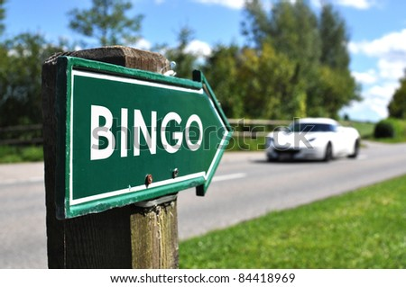 BINGO sign against sportive car on the rural road - stock photo