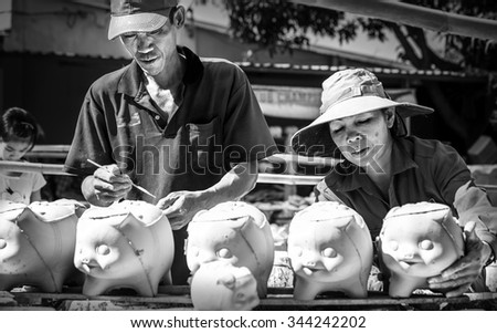 Binh Duong, Vietnam - October 25th, 2015: Family with piggy profession, husband check drawn on itself piggy, wife carrying piggy exposed, girl piggy parts parents in morning sun Binh Duong, Vietnam