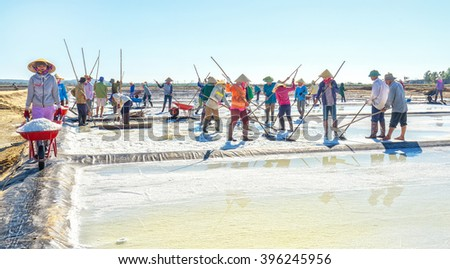 Binh Thuan, Vietnam - January 22nd, 2016: Fishermen raking salt group with rhythmic movements heaps salt clusters for collecting point for processing plants morning coastal  in Binh Thuan, Vietnam - stock photo