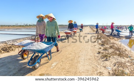 Binh Thuan, Vietnam - January 22nd, 2016: Group fishermen go vertical salt transported to dormitory with smiling face excited harvest is beauty casual labor in morning region sea Binh Thuan, Vietnam - stock photo