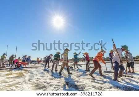 Binh Thuan, Vietnam - January 22nd, 2016: Group of fishermen are raking salt in the sun rhythm Early harvest promises a lot of salt in the coastal countryside Binh Thuan, Vietnam - stock photo