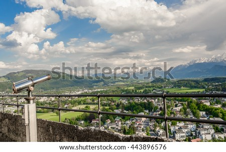Binocular telescope (binoscope) on the top of observation deck - view to the mountains landscape - city at the foot of the Alp under clouds on background