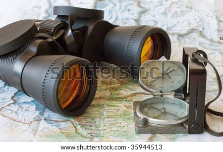 binoculars and magnetic compass on the opened map - stock photo