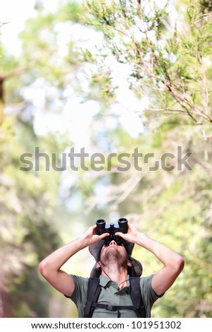 Binoculars - man hiker looking up at copy space during outdoors hiking trip. - stock photo