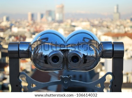 Binoculars telescope looking panorama of Milan from the roof of the Duomo cathedral, Lombardy, Italy - stock photo