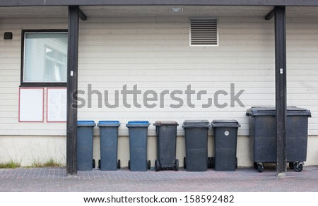 bins standing against the wall - stock photo