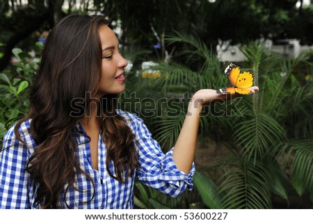 biodiversity: butterfly sitting on the hand of a young woman in the forest - stock photo