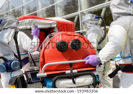 Biohazard medical team pushing stretcher towards decontamination chamber - stock photo