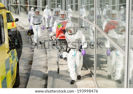 Biohazard team with stretcher wear protective uniform walking outside building - stock photo