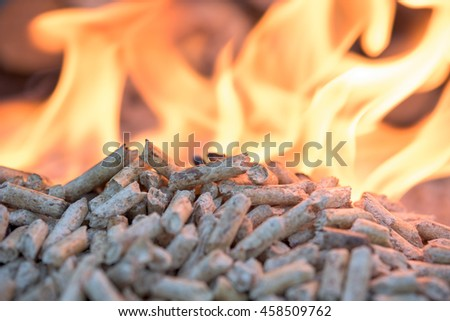 Biomass in flames- oak pellets, close up - stock photo