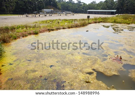 Bioremediation pond for soil contaminated with crude oil at an oilfield in the Ecuadorian Amazon. With oil well in background. - stock photo