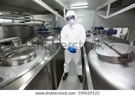 biotechnology specialist in protective uniform,mask,goggles,gloves and wellies in laboratory - stock photo