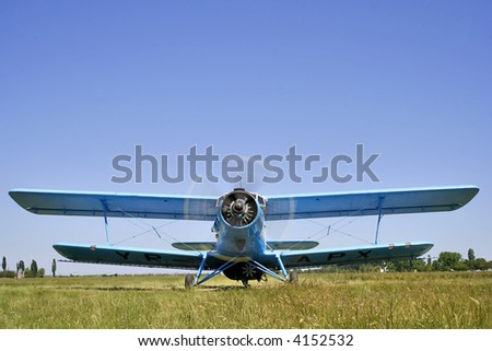 biplane before take-off isolated on blue sky - stock photo