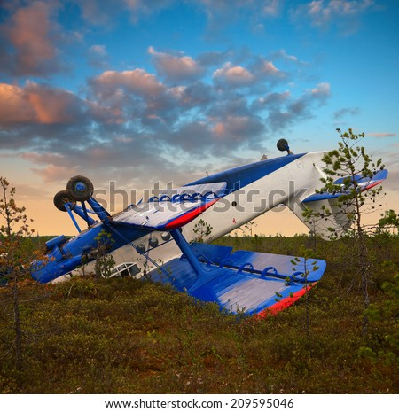 Biplane had crashed in marsh due to engine failure. Plane had rotation after emergency landing on the marsh. It lay up landing gear. - stock photo