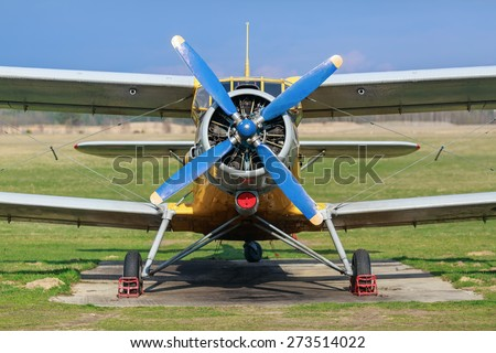 Biplane with blue blue propeller. Old plane close-up. Front view, with the side of the fuselage. Clear sunny day. - stock photo