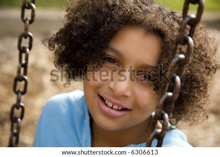 Biracial girl on a swing - stock photo