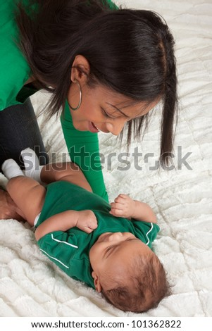 Biracial mom on bed with her multiethnic black infant son (baby is 3 months old) - stock photo