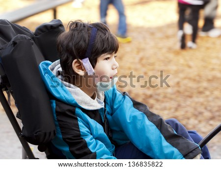 Biracial six year old disabled boy sitting in wheelchair while playing on playground. He has cerebral palsy. - stock photo