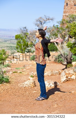 Biracial teen girl raising arms in praise at the Grand Canyon, happy expression - stock photo