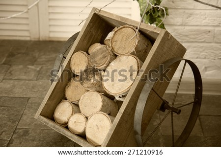 Birch logs in a wooden cart with iron wheels. - stock photo