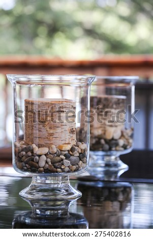 Birch tree candles in glass holders adorn the outdoor table at the cottage.  Perfect Muskoka decor. - stock photo