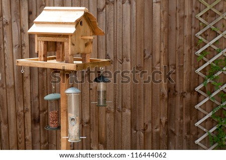 Bird Feeding Table with nuts and seeds hanging from it against a wooden fence with a trellis on it - stock photo