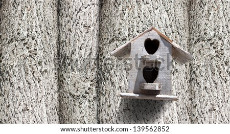 Bird house with the entrance hole with trees. - stock photo