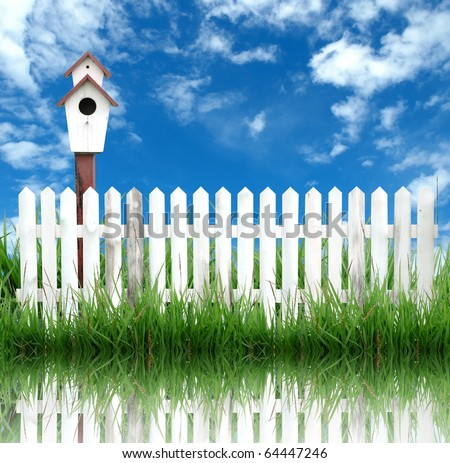 bird house with white fence and blue sky - stock photo
