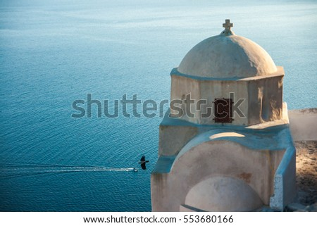 Bird near a picturesque little white church in Santorini over the sea at sunset