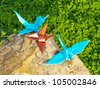 Bird Origami family are resting on the cliff over the green plant - stock photo
