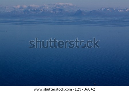 Bird's eye view of blue arctic sea with mountainous coast of Norway in the background - stock photo