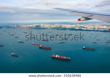 Bird's-eye view seascape with cargo ship in the morning from window of airplane with cityscape background. - stock photo
