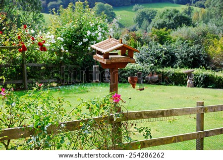 Birdhouse with flowers of pastoral garden in Cotswolds, England