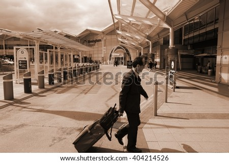 BIRMINGHAM, UK - APRIL 19, 2013: Traveler hurries on April 19, 2013 at Birmingham International Airport, UK. With 8.9 million travelers served it was the 7th busiest UK airport in 2012. - stock photo