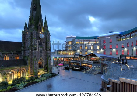 BIRMINGHAM, UK - JANUARY 30: Night scene in downtown Birmingham, UK on January 30, 2012 with the parish church St. George in the Bullring and part of the Bullring Shopping Center. - stock photo