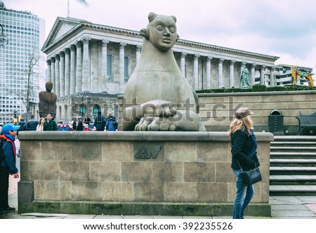 BIRMINGHAM, UK - MARCH 5 2016: Tourist stands for a picture by Victoria Square's Sphinx statue, in the background the Town Hall building - stock photo