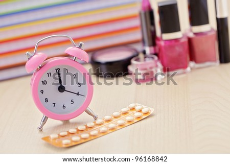 birth control pill with alarm clock - healthcare and medicine - stock photo