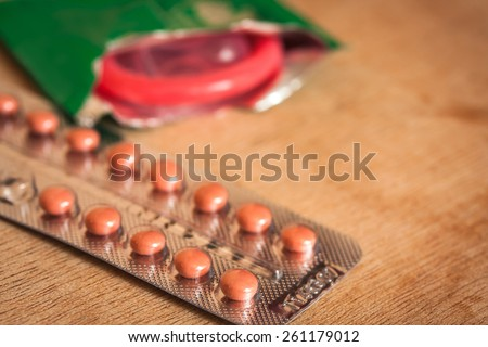 birth control pills and condom on wooden table background.soft and selective focus.  - stock photo