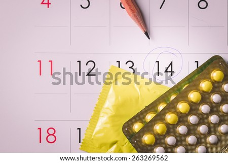 Birth control pills on calendar (add vignette tone) - stock photo