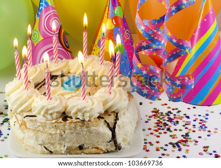 birthday cake and candles against colorful party background - stock photo